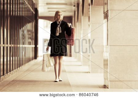 Happy young fashion woman with shopping bags at the mall window