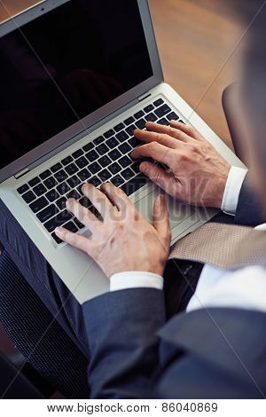 Man working with laptop on knees.