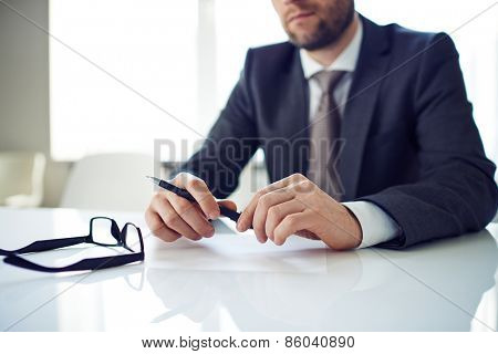 Man with pen thinking about work