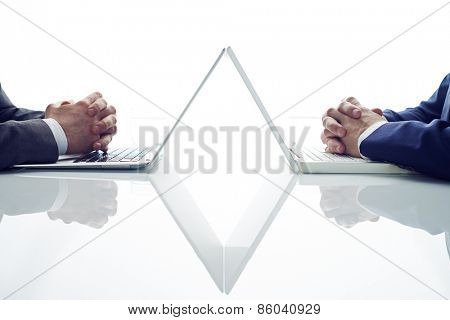 Two businessmen with joining fingers sitting opposite
