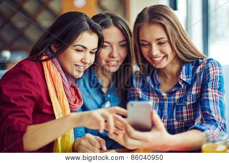 Smiling girls looking through photos in telephone