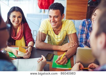 Smiling students having conversation with their friends