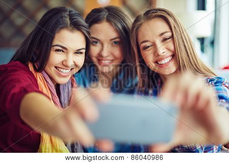 Happy girls taking photo with mobile cell phone