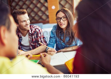 Girl in glasses explaining topic to friends