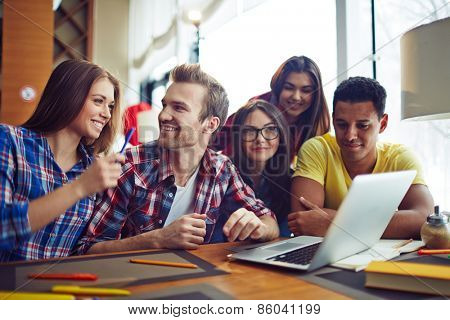 Five students looking at laptop
