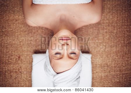 Young woman lying with towel on her head