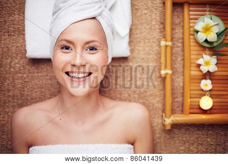 Woman lying on massage table and smiling