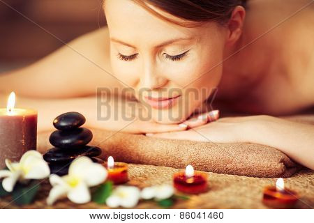 Woman relaxing among candles and flowers