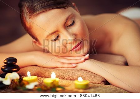 Woman lying on towel at beauty spa