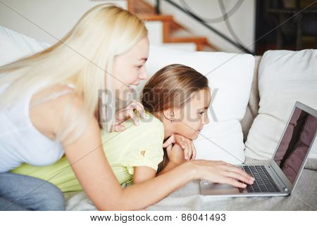 Pretty mother and daughter sitting on sofa and looking at computer