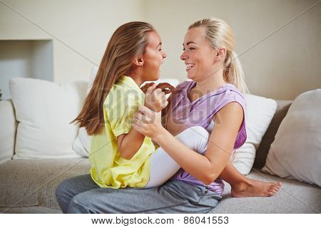 Mother and daughter sitting on couch and playing