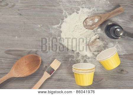 Various baking tools from overhead view on wooden table in vintage tone, copy space on top.