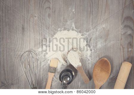 Baking tools from overhead view on wooden table in vintage tone, copy space on top.