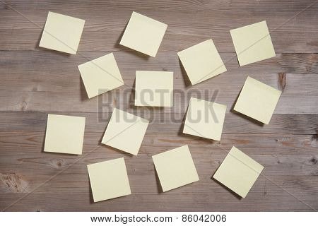 Sticky notes on wooden background, in vintage tone.