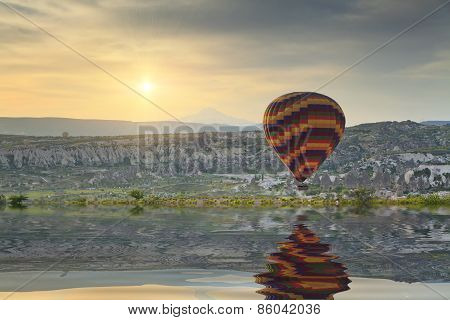 Reflection Balloon Flying In The Lake At Sunset.
