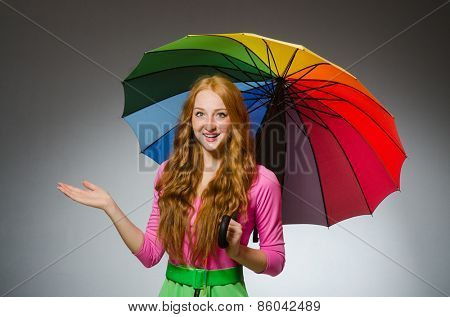 Woman holding colourful umbrella in studio