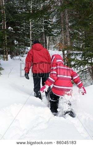 Woman And Kid Snowshoeing