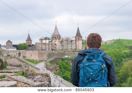 Man, traveler sitting on the edge of a cliff and watching peaceful landscape. Tourists visiting Ukra