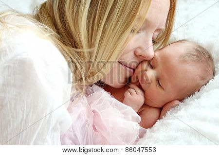 Happy Mother Snuggling Newborn Baby In Bed