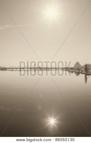 Sepia photo of Riga bridge and sun with reflection in Daugava