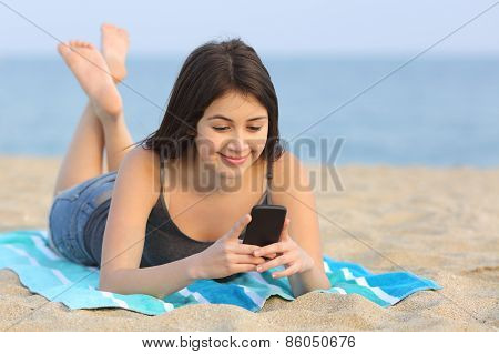 Teenager Girl Texting A Smart Phone Lying On The Beach