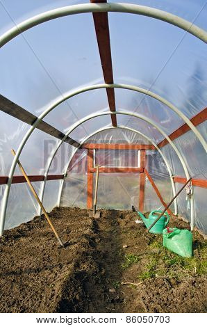 Early Spring  Greenhouse Inside Construction With Gardener Tools And  Soil