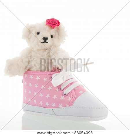 White hand made teddy bears and pink baby shoes isolated over white background