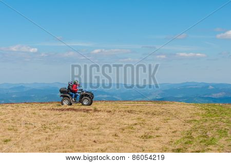 Quad biking in the mountains. Equipped ATV driver and passenger. Landscape, spring