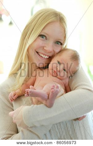 Happy Young Mother Holding Cuddly Newborn Baby