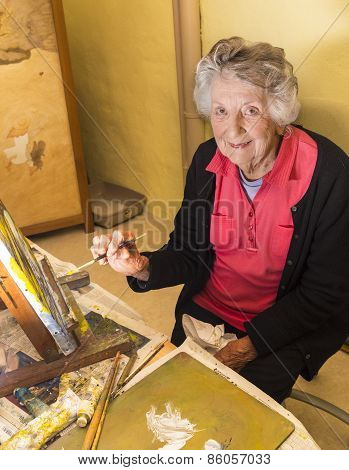 Senior Woman Painting At Her Easel In Her Studio In France