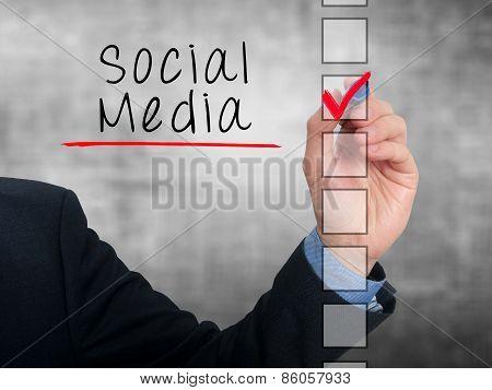 Businessman hand writing Social Media and check listing task.