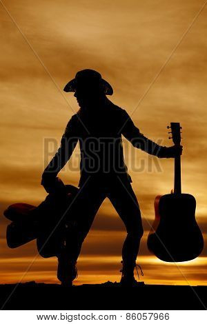 Silhouette Of Woman With Saddle And Guitar Standing