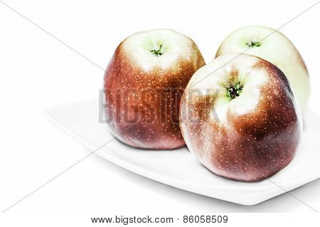 Three red apples on a white plate and a white background