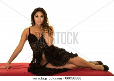 Woman In Black Lingerie Sitting On Red Sheet Looking