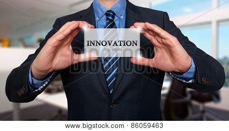 Businessman holding white card with Innovation sign.- Stock Photo