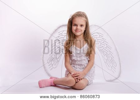 Sitting Girl In An Angel Costume On A White Background