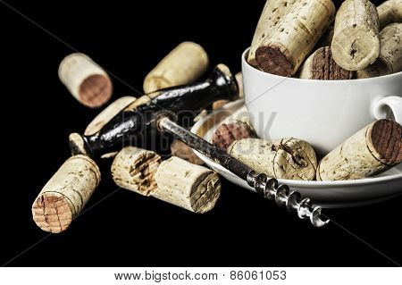 Close-up of wine corks and corkscrew on a black background