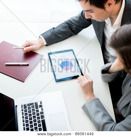 Businessman And Businesswoman, Analysing A Statistical Business Pie Graph On A Tablet Computer