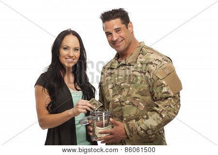 Young Couple Collecting Money In Jar