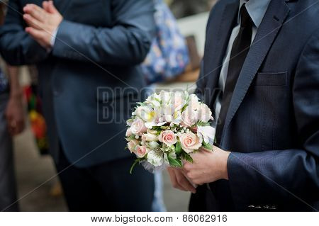 Pastel wedding bouquet with roses in groom's hands