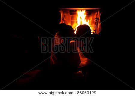 Silhouette couple kissing near the fireplace
