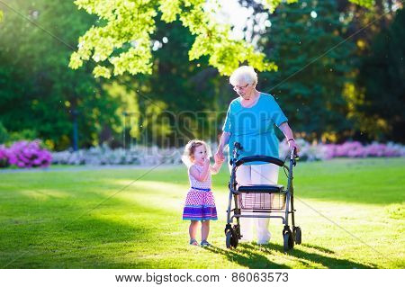 Senior Lady With A Walker And Little Girl In A Park