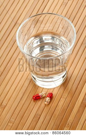Glass Of Water And Medicine Pills On Wooden Background