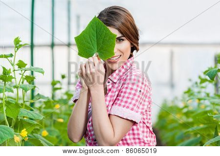 Portrait of woman holding a green leaf
