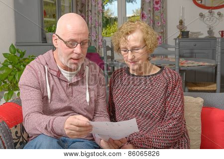 A Mother And Her Adult Son Looking A Paper