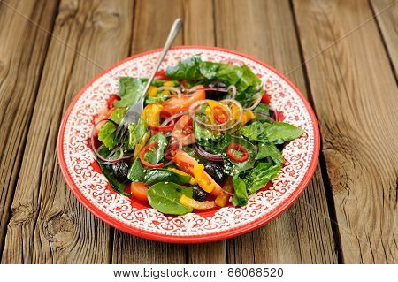 Green Salad With Raw Vegetables: Spinach, Tomatoes, Olives, Onion, Bell Pepper In Red Plate