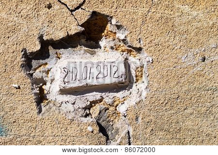 Bricks Laid In An Old Wall With The Date Of The Bookmark. Dirty Concrete Wall With Cracks And Scratc
