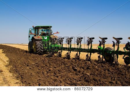 Agricultural Tractor Plowing A Field