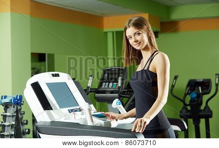 Cute girl exercising on simulator in gym