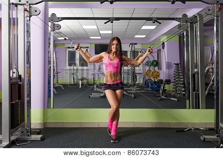 Athletic woman with perfect body posing in gym